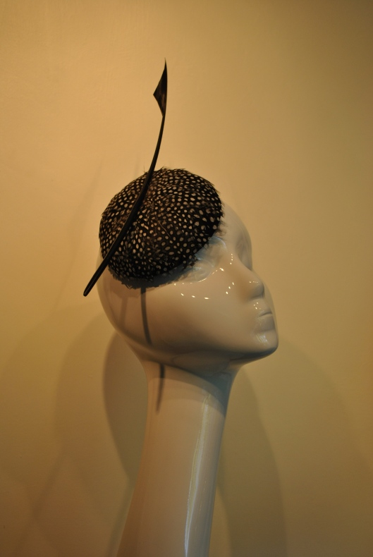 Spring/Summer13 felt button shaped cocktail hat covered with guinea fowl feathers and adorned with a goose spear.
